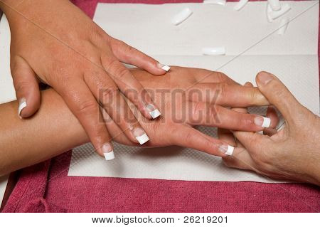 Manicurist installing fake nails