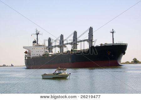 A large container ship on the Sacramento Delta in California passing a small fishing boat