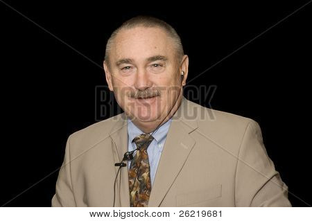 older businessman in a suit with cell phone earpiece isolated on black