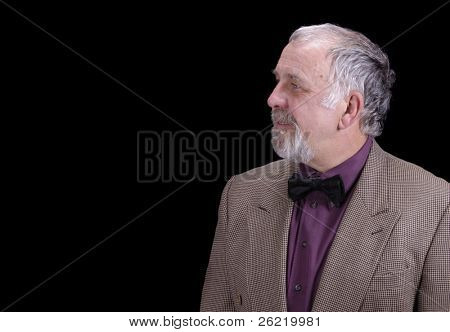 older bearded businessman looking off to the right into copy space, isolated over black