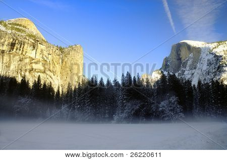 Sunset on the granite peaks in Yosemite National Park with mist rising from the snow cover floor in the valley, an airliner leaving a trail in the sky and snow on top of Half dome.