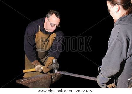 Blacksmith working on decorative handrail beating the heated metal with a sledge hammer