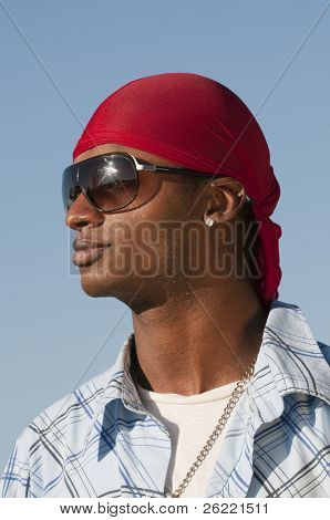 young smiling African American man with a red bandanna on his head and sunglasses on over a blue sky
