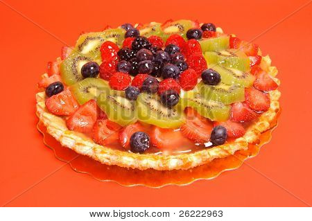 Glazed fruit flan or pie on a red orange background