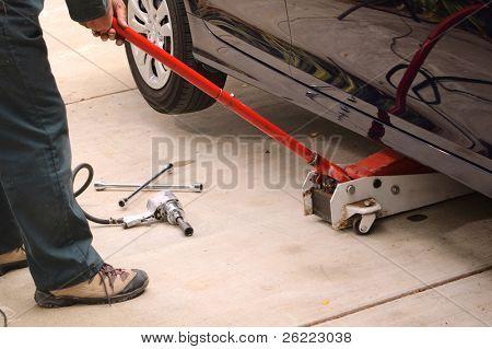 Mecânico de carro usando várias ferramentas para trocar os pneus de um veículo a trabalhar.