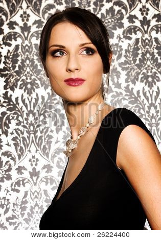 a portrait of a beautiful brunette woman wearing black shirt on background with pattern