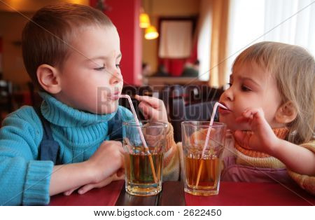 Little Boy And Girl Drink Juice From Glasses Through Straws