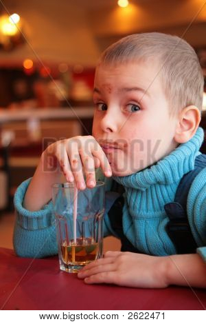Soiled Boy Drinks Juice From Glass Through Straw