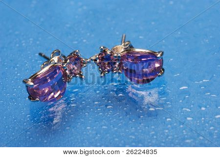 a pair of silver earrings with purple stone on blue background with water drops