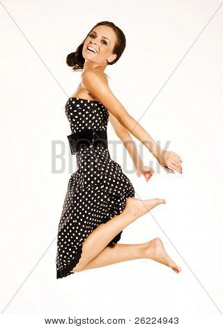 a beautiful brunette girl wearing a dress jumping up on white background