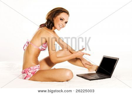 beautiful woman wearing bikini with a laptop
