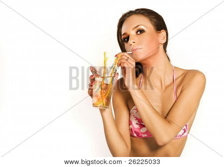 a beautiful brunette girl wearing pink bikini drinking a cocktail on white background