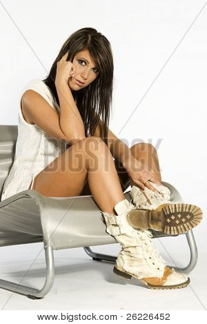 bella y sexy morena vestida de blanco sentada en la silla de plata