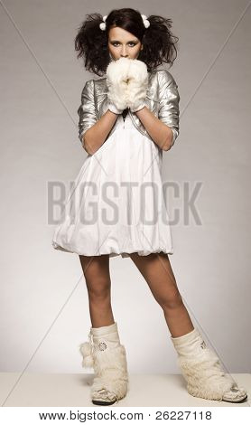 beautiful brunette winter girl wearing furry gloves and boots on light background