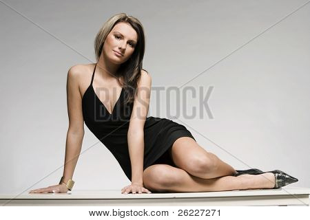 beautiful blonde girl wearing black mini dress posing on grey background