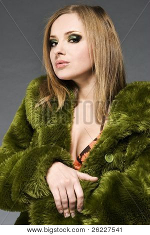 attractive blonde model wearing green fur and bikini with green make-up