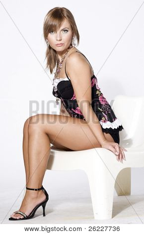beautiful blonde moder wearing black and pink lingerie posing on light background