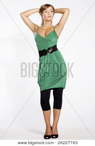 attractive and sexy blonde woman wearing green dress and black leggins on light background
