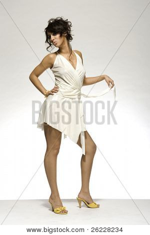 beautiful brunette girl wearing white dress and yellow shoes on light background