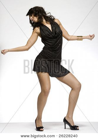 beautiful brunette wearing black dress on light background