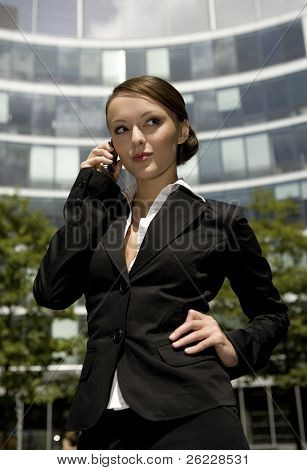 young and attractive businesswoman talking on the mobile outside