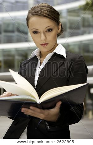 young brunette businesswoman outdoors with a notebook