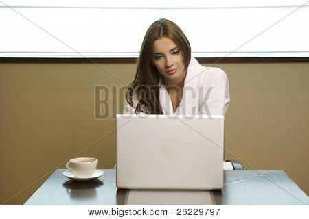 Young woman looks at her laptop computer and drinks her coffee. It is early morning in a light and clean home interior dominated by white and soft tones.