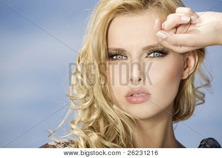 portrait of beautiful blonde girl on background blue sky