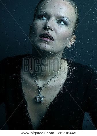 Woman face behind glass with rain drops