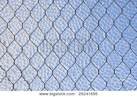 Close-up image of wire-reinforced glass window. Abstract background