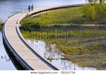 Bicyclists are riding along the boardwalk. Evening scene in a city park, Carmel, IN