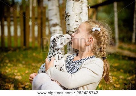 Cute Girl Kissing Her Puppy