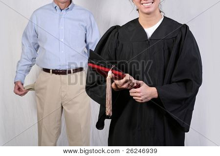 conceptual shot of a father standing behind his graduating daughter showing that his pockets are empty; he is broke