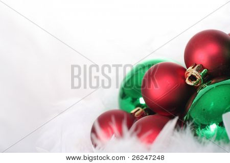 Red and green Christmas ornaments on soft billowy feathers
