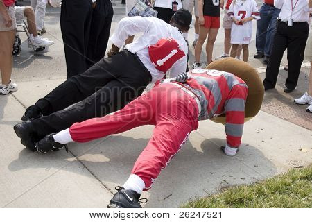 Brutus and a fan do a one arm push-up before the game