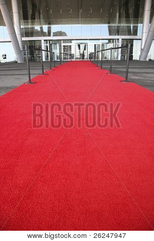 Red carpet celebrity entrance into a glass building