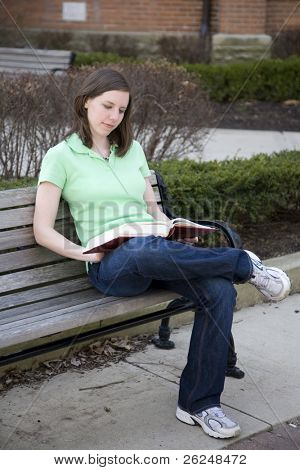 Attractive college student reading outside on a bench