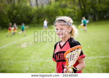 Jogador de lacrosse com o jogo acontecendo em segundo plano