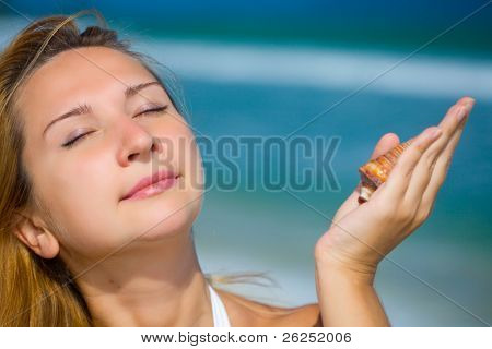 Young woman with seashells on the tropical beach