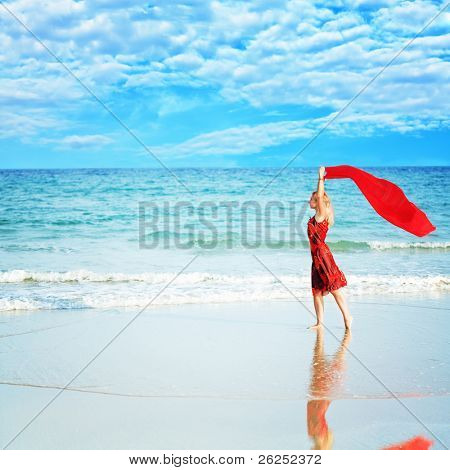 Beautiful woman walking near the ocean with red sarong