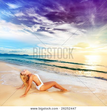 Woman sunbathing on the beach at sunrise time