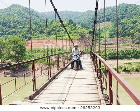 Wooden bridge over mountain river. Northern Vietnam