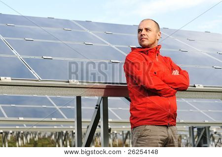 Young male worker with solar panels in background