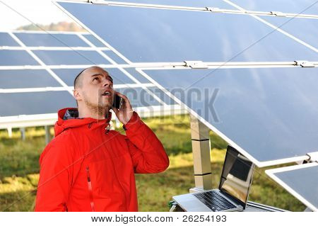 Engineer working with laptop by solar panels, talking on cell phone