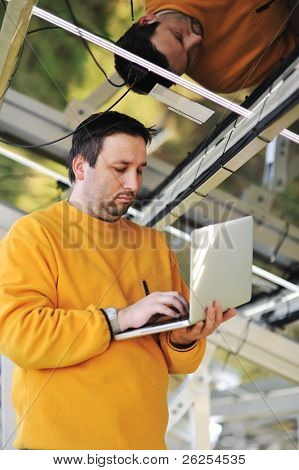 Engineer using laptop and connecting wires at work place