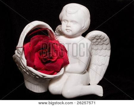 love gift with ceramic angel figure and red artificial rose on black