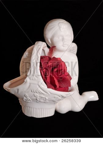 love gift with ceramic angel figure and red artificial rose isolated on black