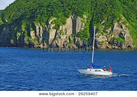 motor yacht sailing against the rocky coast