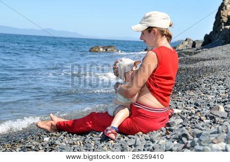 mother breastfeeding her baby on the sea beach