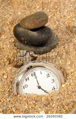 watch in the sand and stones pyramid. time concept